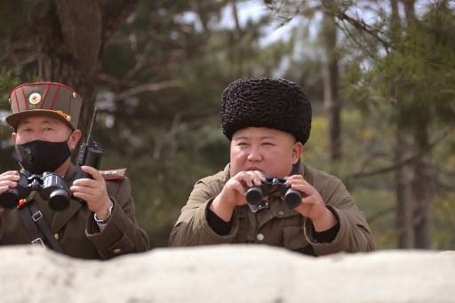 Pemimpin Korea Utara Kim Jong Un mengawasi latihan bersama dengan seorang perwira tinggi yang mengenakan masker di Korut.  (FOTO: STR / KCNA MELALUI KNS / AFP)