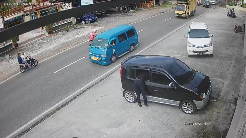 Pelaku saat mengambil barang dari jok belakang mobil ibu-ibu di Agam Sumbar (Wahyu Sikumbang/iNews)
