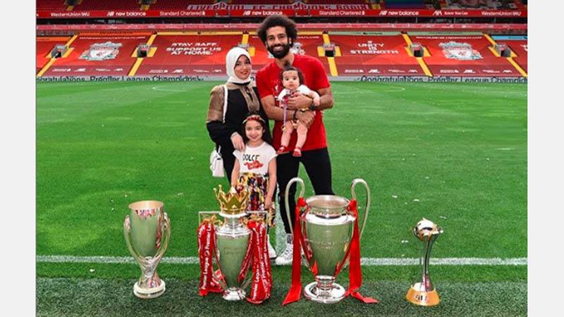 Mohamed Salah mengajak istrinya, Magi, dan kedua putri mereka, berfoto bersama empat trofi yang diraih Liverpool musim ini. (Foto: Instagram @mosalah)