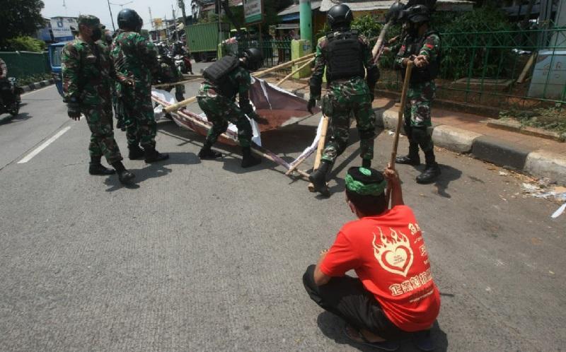 Prajurit TNI dan personel gabungan menurunkan baliho bergambar Habib Rizieq Shihab di kawasan Petamburan, Jakarta, Jumat (20/11/2020) karena dianggap menyalahi izin. (Foto: SINDOnews/Eko Purwanto)