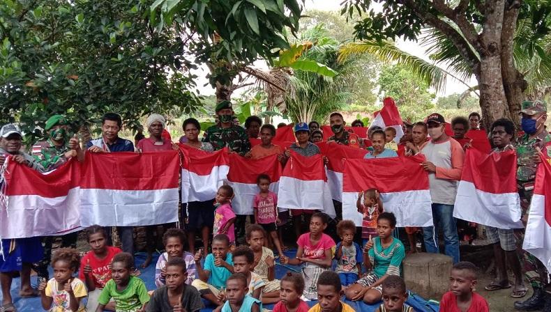 Sambut HUT RI, Satgas Yonif 125 Bagikan Bendera Merah Putih kepada Warga Distrik Sota