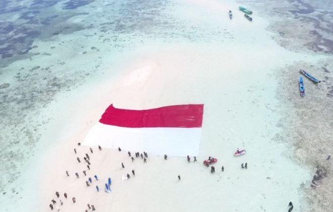 Prajurit Lantamal VIII Manado Bentangkan Merah Putih di Pasir Timbul Pulau Nain